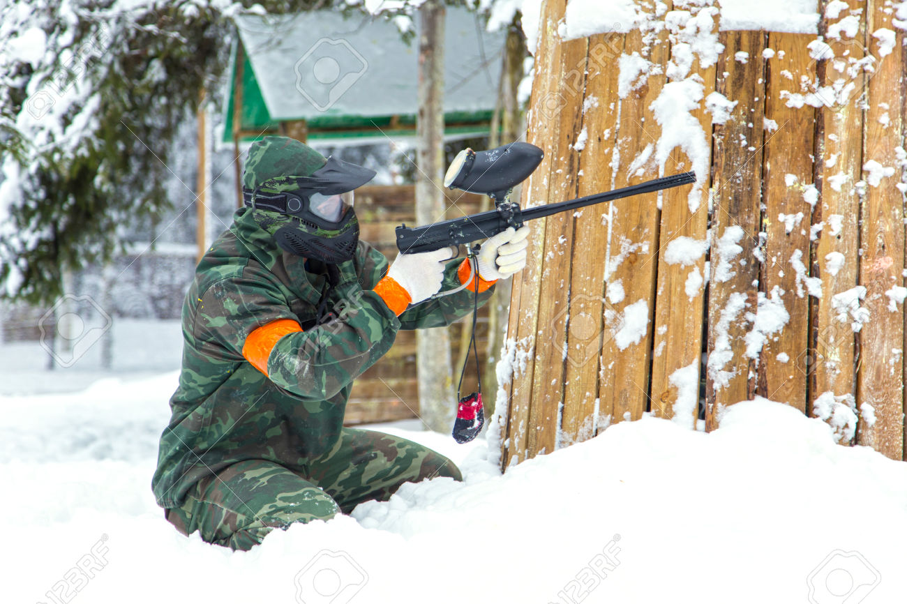 Paintball player sitting on snow near wooden fortification and shooting